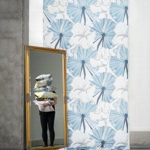Kuviollinen sininen verho ja peilistä heijastuva tyynypino